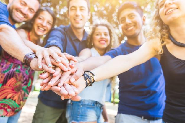 Grupa przyjaciół z rękami na stosie