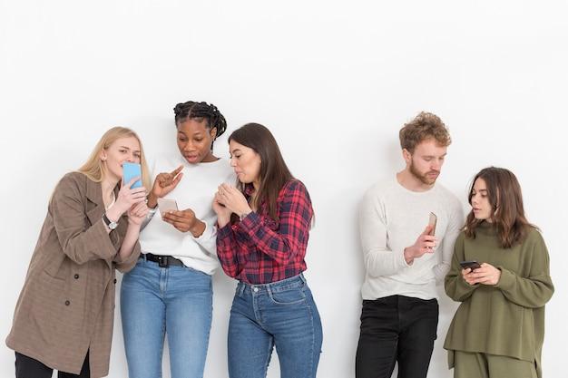 Grupa przyjaciół z telefonami komórkowymi