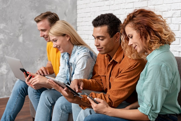 Grupa przyjaciół z urządzeniami elektronicznymi