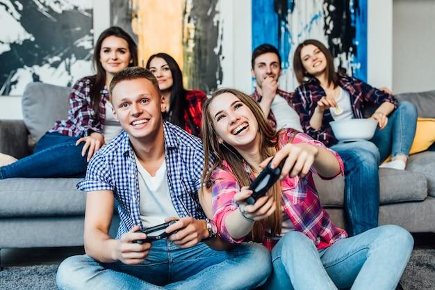 Grupa przyjaciół zabawy grając w gry wideo, siedząc na kanapie w domu. koncepcja dotycząca technologii, gier wideo, stylu życia i ludzi