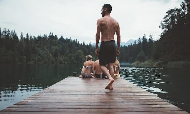 Grupa przyjaciół zabawy nad jeziorem w godzinach porannych