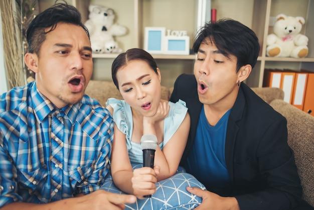 Grupa przyjaciół, zabawy w salonie śpiewając piosenkę razem