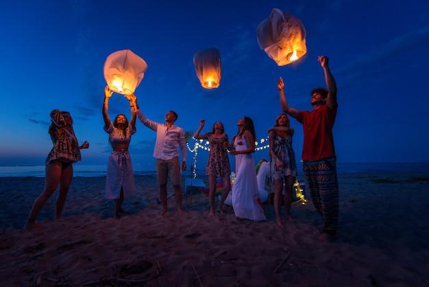 Grupa przyjaciół zapalających latarnie