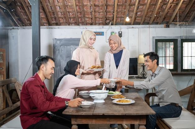 Grupa przyjaciół zbiera się i je razem w jadalni