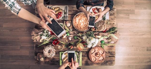 Grupa przyjaciół zrób zdjęcie telefonem komórkowym przed obiadem. widok z góry.
