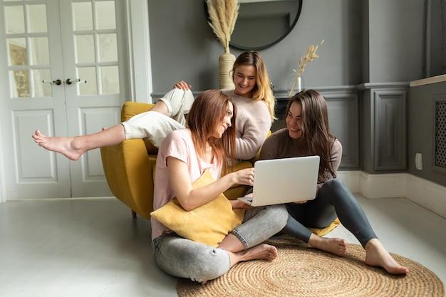 Grupa przyjaciółek komunikuje się z przyjacielem za pośrednictwem wideokonferencji na laptopie. przyjaźń