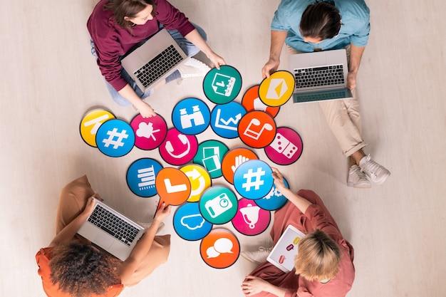 Grupa przyjaznych międzykulturowych millenialsów z gadżetami mobilnymi, dyskutujących na papierze o ikonach sieci społecznościowych, siedząc na podłodze