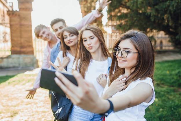 Grupa przystojnych młodych ludzi robi selfie w kampusie.