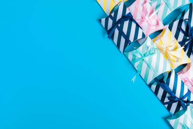 Grupa pudeł prezentowych ze wstążką umieszczoną na niebieskim tle