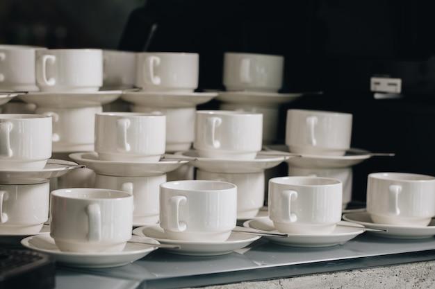 Grupa pustych filiżanek kawy. wiele rzędów białych filiżanek do serwowania herbaty lub kawy na śniadanie lub w formie bufetu i seminarium. biały kubek w gastronomii i koktajlu.