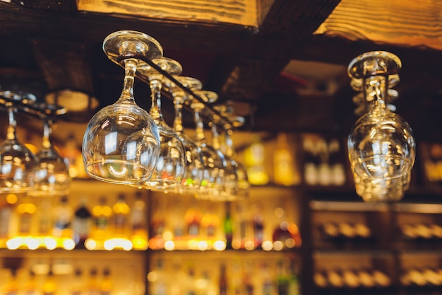Grupa pustych kieliszków do wina wiszące z metalowych belek w barze.