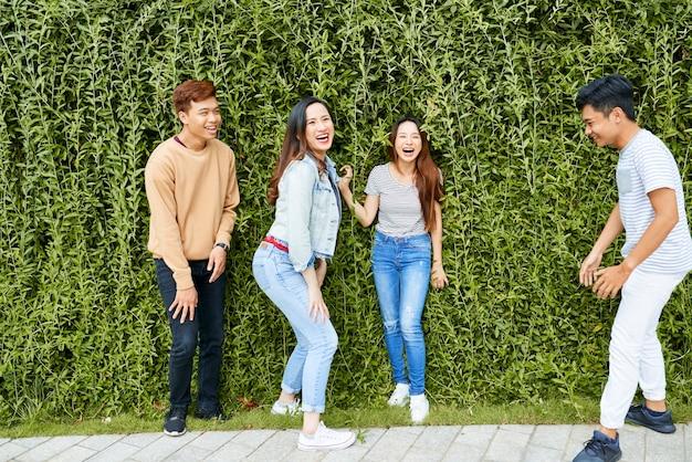 Grupa radosnych młodych ludzi śmiejących się podczas pozowania do zdjęcia przed zielonym żywopłotem