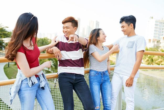 Grupa radosnych młodych ludzi stojących na moście, śmiejących się i żartujących