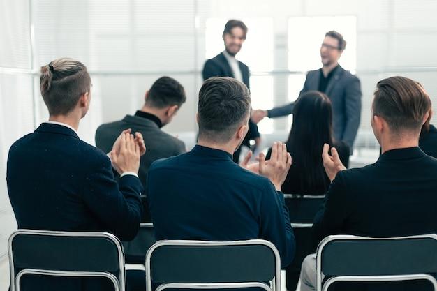 Grupa robocza oklaskiwała partnerów biznesowych podczas spotkania. spotkania i partnerstwa