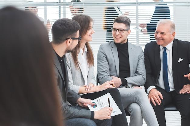 Grupa robocza omawia swoje pomysły siedząc w sali konferencyjnej. pomysł na biznes