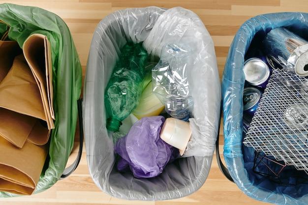 Grupa różnego rodzaju śmieci w plastikowych torebkach na drewnianym stole