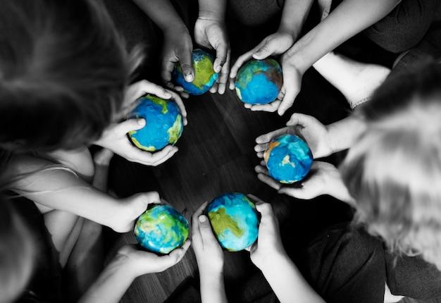 Grupa różnorodni dzieciaki wręcza trzymać cupping kul ziemskich piłki wpólnie