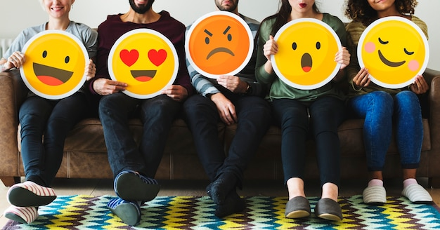 Grupa różnorodni ludzie trzyma emoticon ikony