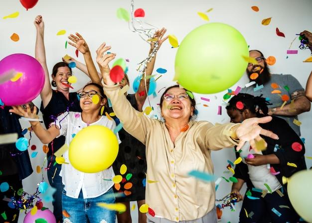 Grupa różnorodni ludzie z przyjęcie balonów confetti