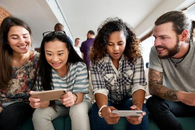 Grupa różnorodni przyjaciele bawić się grę na telefonie komórkowym
