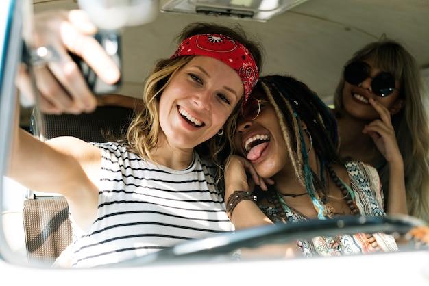 Grupa różnorodni przyjaciele na wycieczce samochodowej bierze selfie wpólnie