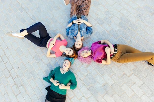 Grupa różnorodności młode kobiety kłama na podłoga i przygląda up
