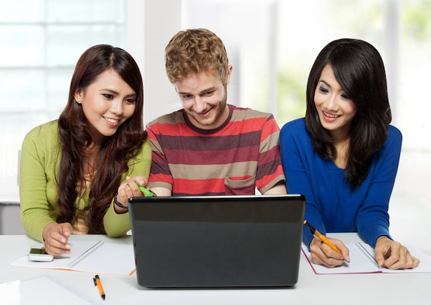 Grupa różnorodności szczęśliwi ucznie studiuje wpólnie używać laptop