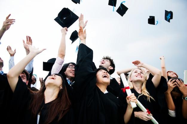 Grupa różnorodnych absolwentów rzuca nakrętki up w niebie