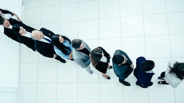 Grupa różnorodnych ludzi biznesu stojących w kolejce