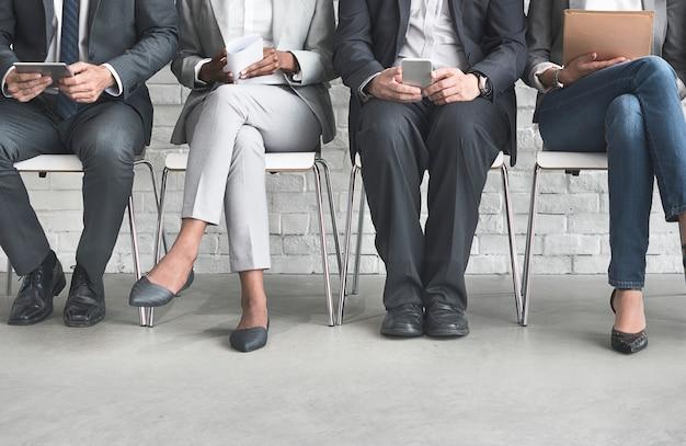 Grupa różnorodnych ludzi czeka na rozmowę o pracę
