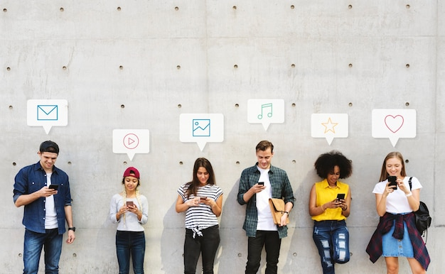 Grupa różnorodnych ludzi korzystających ze swoich telefonów