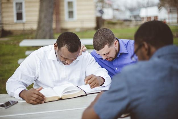 Grupa różnorodnych ludzi siedząca przy stole i czytająca biblię