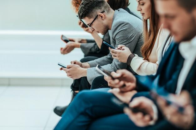 Grupa różnorodnych młodych ludzi siedzących w rzędzie ze smartfonami