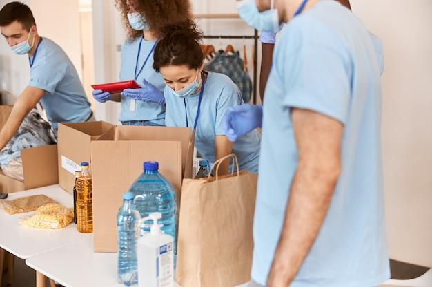 Grupa różnorodnych osób noszących niebieskie, jednolite maski ochronne i rękawiczki, sortująca podarowane artykuły spożywcze
