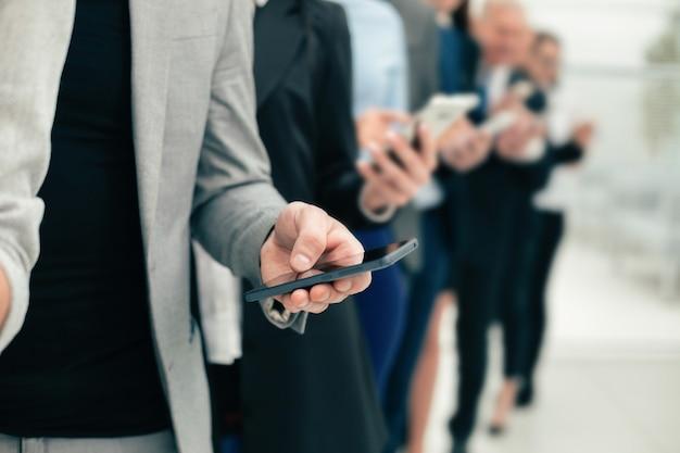 Grupa różnorodnych pracowników ze smartfonami stojącymi w rzędzie