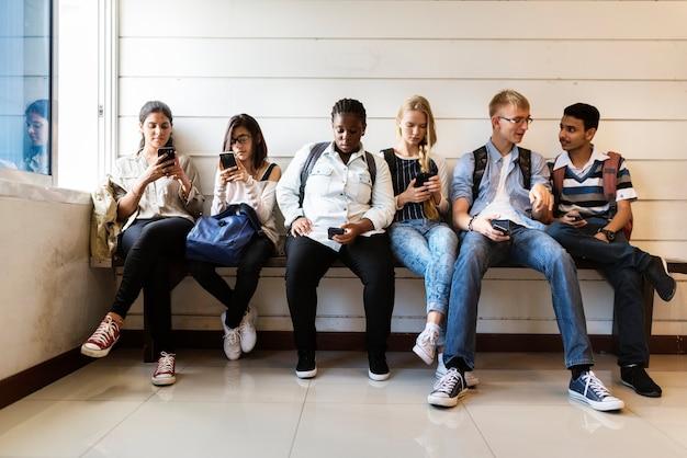 Grupa różnorodnych uczniów korzystających z telefonów komórkowych
