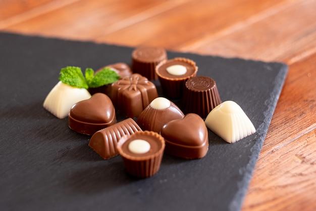 Grupa różnych czekoladek, mlecznych i ciemnych, na czarnym tle.