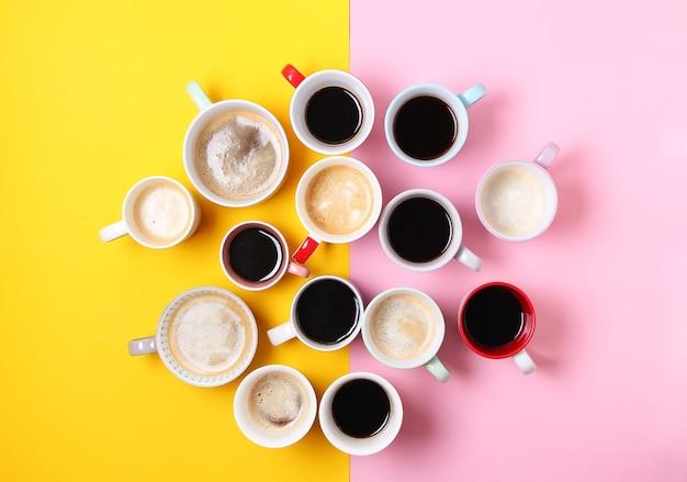 Grupa różnych filiżanek kawy na tle żółtym i różowym. widok z góry, płaski układ, miejsce na kopię.