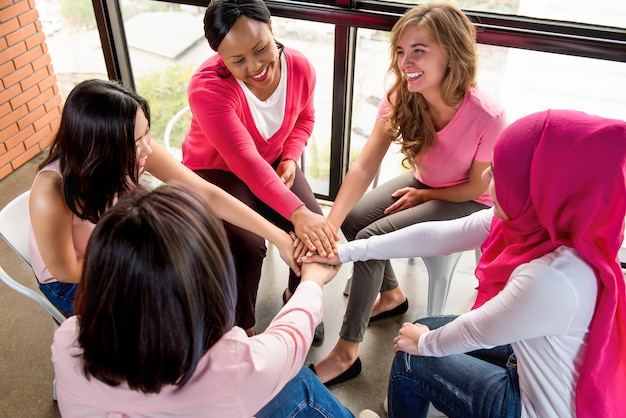 Grupa różnych kobiet układa ręce, wzmacniając siebie nawzajem