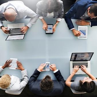 Grupa różnych ludzi biznesu używa urządzeń cyfrowych