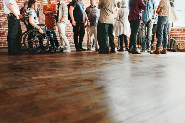 Grupa różnych ludzi stojących przed ceglanym murem