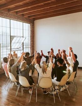 Grupa różnych ludzi trzymających ręce w powietrzu