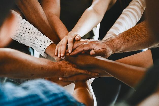 Grupa różnych ludzi układających ręce pośrodku