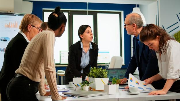 Grupa różnych przedsiębiorców, spotkanie pomysłów burzy mózgów na temat nowego projektu finansów dokumentacji, współpracownicy współpracujący ze sobą planowanie strategii sukcesu pracy zespołowej siedząc przy biurku w nowoczesnym biurze.