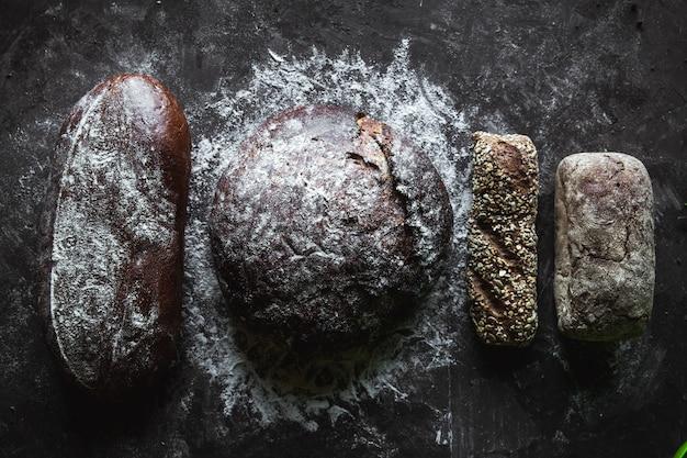 Grupa różnych rodzajów chleba na czarnym tle
