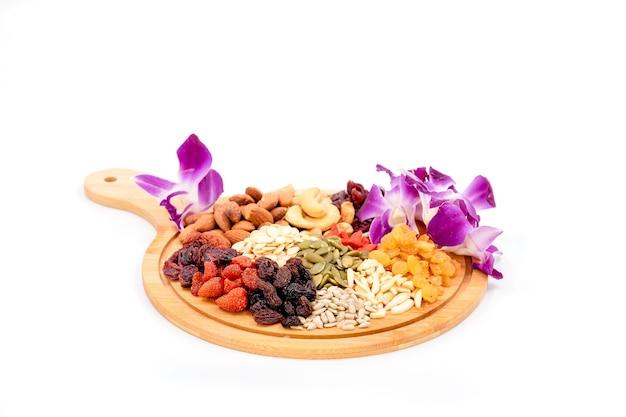 Grupa różnych rodzajów suszonych owoców i suszonych ziaren z piękną orchideą na drewnianym talerzu na białym tle.