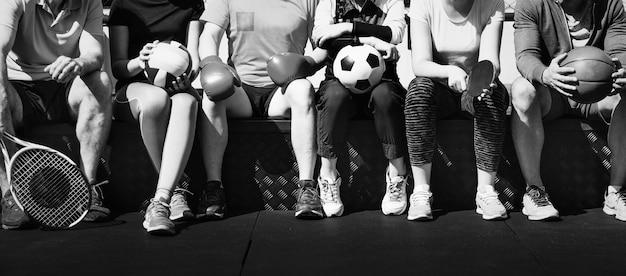 Grupa różnych sportowców siedzących razem