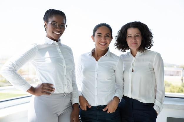 Grupa rozochoceni bizneswomany ono uśmiecha się przy kamerą
