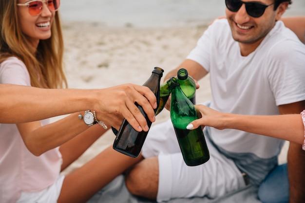 Grupa rozochoceni przyjaciele robi grzance, podczas gdy relaksujący na plaży, radośnie ono uśmiecha się