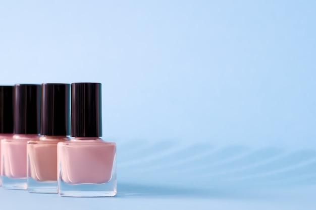 Grupa różowych lakierów do paznokci na niebieskiej powierzchni.